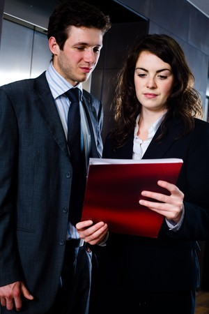 Young businesspeople working together at office corridor, looking at red document folder, reading reports. Stock Photo - 4244958