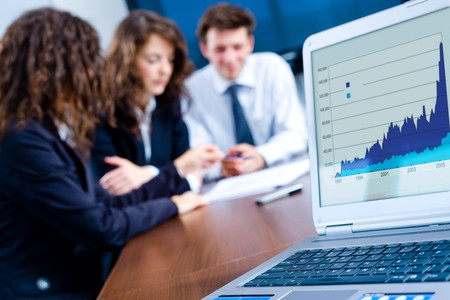 In background happy young business people having meeting at office. In front focus placed on graph shiwing progress on laptop screen. Stock Photo - 4244834
