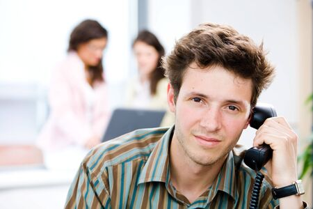 Young businessman receiving phone calls at office while business people team working in background. Stock Photo - 4244857