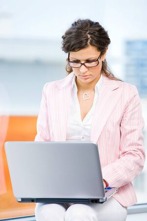 Young attractive businesswoman working on laptop computer in fron front of office window. Stock Photo - 4244782