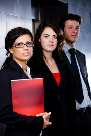 Portrait of successful happy business team posing at office lobby in front of elevator. Dark background. Stock Photo - 4244784