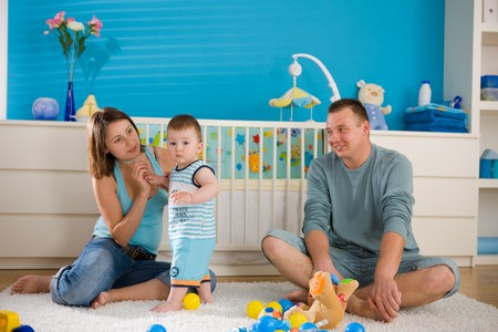 Portrait of happy family at home. Baby boy ( 1 year old ) and young parents father and mother sitting on floor and playing together at children's room, smiling. Stock Photo - 4244896