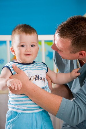 Happy baby boy ( 1 year old ) and father playing together at children's room, smiling. Stock Photo - 4244944