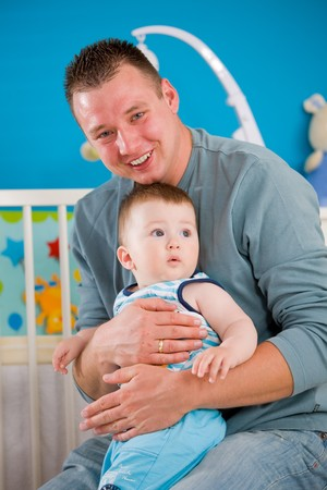 Portrait of baby boy ( 1 year old ) and father at children's room, smiling. Stock Photo - 4244959
