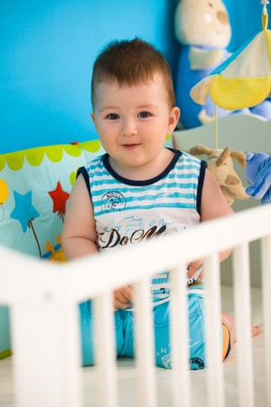 Happy baby boy ( 1 year old ) playing in baby bed at childrens room, smiling. photo