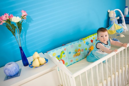 1 year old: Baby boy ( 1 year old ) playing in baby bed at childrens room. Stock Photo