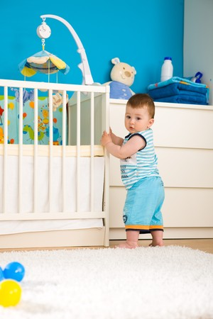 bedrooms: Sweet baby boy ( 1 year old ) standing at childrens room in front of crib. Stock Photo