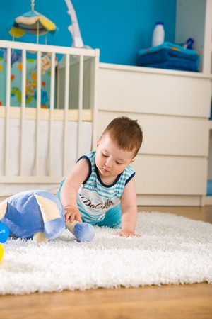 babyboy: Sweet baby boy ( 1 year old ) sitting on floor at home and playing with soft toys at childrens room.