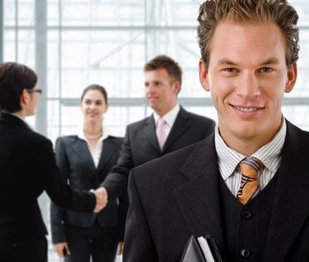 businesswear: Team of business people, businessman in front, handsake in background. Stock Photo