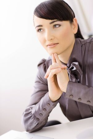 Young businesswoman thinking in her office, interlocking his hands. Stock Photo - 4244712