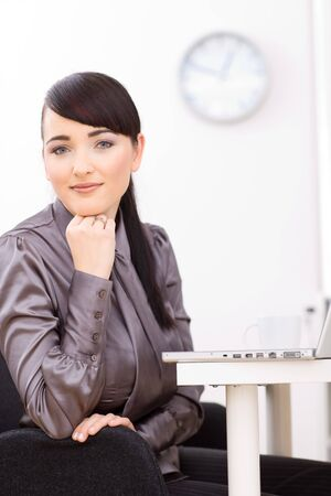undoubting: Young businesswoman thinking at her desk in the office, leaning on her hand.