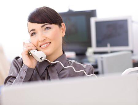 Young female customer service operator talking on landline phone, smiling. Stock Photo - 4244659
