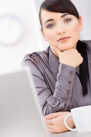undoubting: Young businesswoman thinking in her office leaning on her hand, looking at camera. Stock Photo