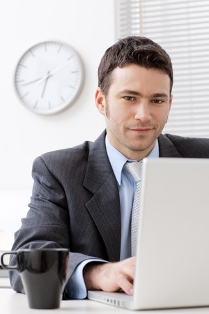 Businessman working on laptop computer at office, smiling. photo