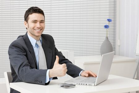 happy businessman: Happy young businessman showing success with thumb up at office, smiling. Stock Photo