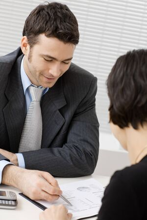Happy young adviser businessman consulting at office, smiling. Stock Photo - 4244855