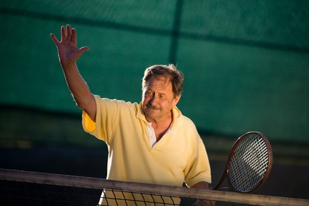 Active senior man in his 70s is posing on the tennis court with tennis racket in hand. Outdoor, sunlight. photo