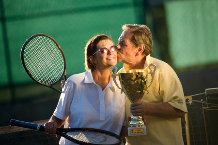 Active senior couple is posing on the tennis court with tennis racket and cup in hand. Outdoor, sunlight. photo