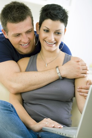Happy young couple browsing internet on laptop computer at home, smiling. photo