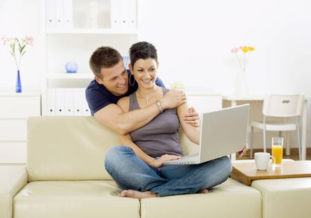 living together: Happy young couple browsing internet on laptop computer at home, smiling.