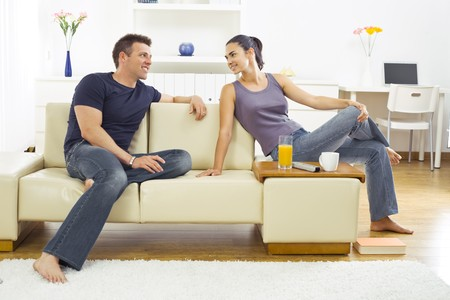 Happy young couple sitting on sofa at home, smiling. Stock Photo - 4245193