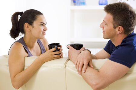 Adult couple sitting on sofa at home drinking coffe, talking, smiling. photo