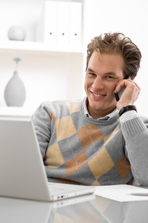 Young man using laptop and calling on phone at home. photo