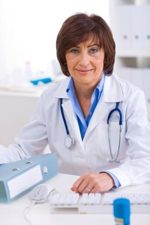 offiice: Senior female doctor sitting at desk working at offiice. Stock Photo