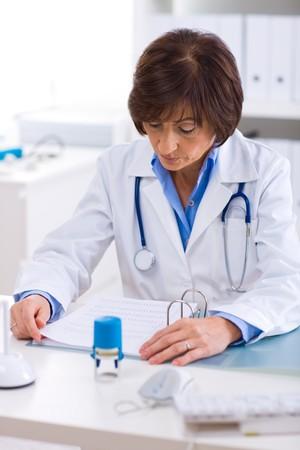 doctora: Superior de las mujeres m�dico en la sesi�n de trabajo en el escritorio offiice.