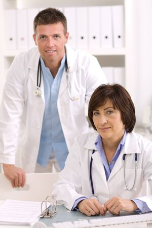 Medical doctors working in team at office, smiling. Focus on female. photo