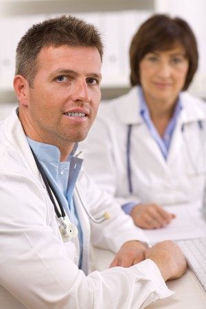 Medical doctors sitting at desk working at office. photo