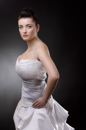 Portrait of a bride posing in a white wedding dress, arms on hips, looking at camera. photo