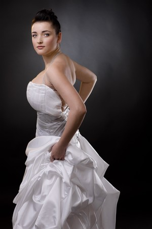Happy bride posing in a white wedding dress, holding her skirt and looking at camera. photo
