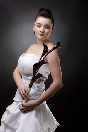Portrait of a bride posing in a white wedding dress, holding purple flowers, smiling and looking at camera. photo
