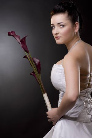Studio portrait of a young bride posing in a white wedding dress, holding purple flowers, looking back. Stock Photo - 4245505