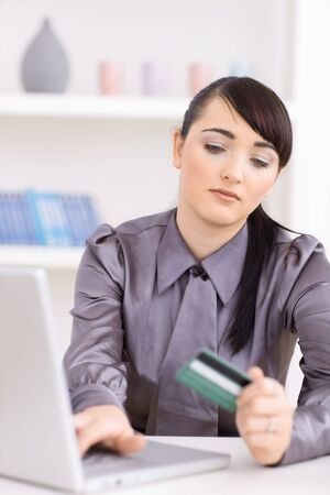 Young women shopping online at home, using laptop computer, holding credit card in hand. photo