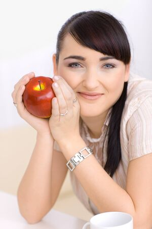 Closeup portrait of beautiful young woman holding red apple in hands, smiling. photo