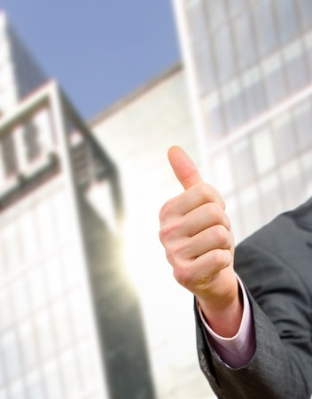officetower: Businessman showing ok with tumb up on hand in front of office building.