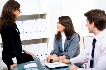 businesswear: Young happy businesspeople talking at office, two sitting on chairs one sitting on table.