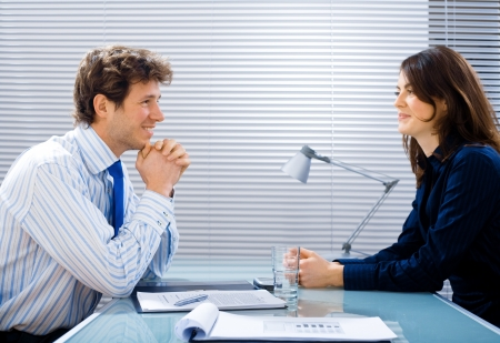 Businessman and businesswoman working together in team at office, smiling. photo