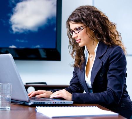persona escribiendo: Feliz joven empresaria de trabajo en ordenador port�til en la oficina, sonriendo. Cielo nublado en la televisi�n sreen. Foto de archivo