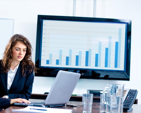 Young businesswoman sitting by meeting table at office in front of a huge plasma TV screen and using laptop and phone.