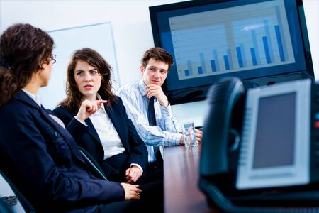 Young serious businesspeople talking in meeting room at office, phone and plasma TV. Stock Photo - 4366455