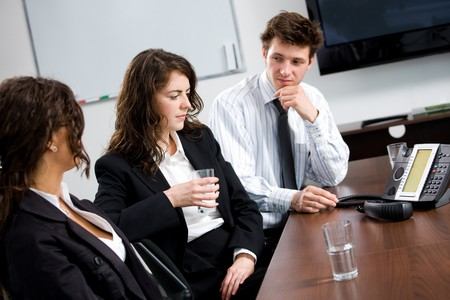 Businesspeople sitting on meeting at office listening phone during a conference call. photo