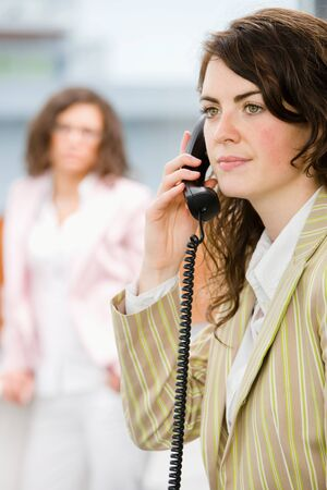 Businesswomen at office, receptionist calling on phone. photo