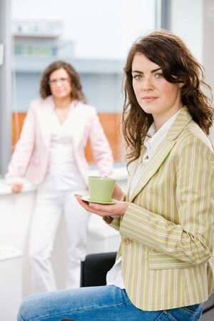 Young businesswomen having break at office drinking coffee. photo