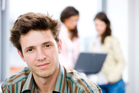 Young happy businessman looking at camera, smiling while business team working in background. Stock Photo - 4366463