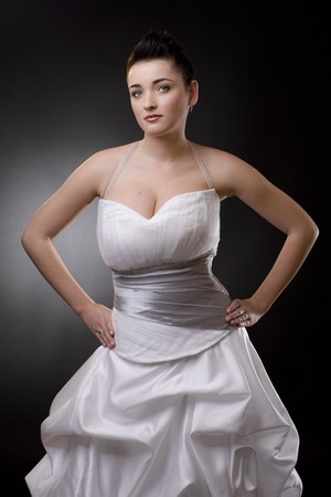 Bride posing in a white wedding dress, arms on hips, looking at camera. photo