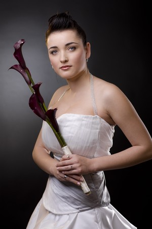 Studio portrait of a bride posing in a white wedding dress, holding purple flowers looking at camera. photo
