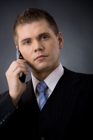 undoubting: Closeup portrait of young businessman talking on mobile phone.